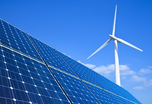 Solar panels and wind turbine against blue sky