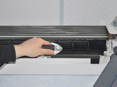 Close up on Air Conditioner Cleaning with Brush