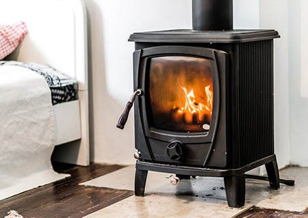 small wood stove burning in bedroom