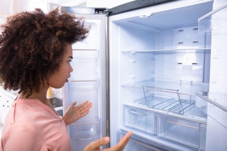 Close-up Of Shocked African Young Woman Looking At Empty Refrigerator