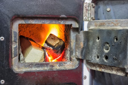 Old stove with open door and burning the woo